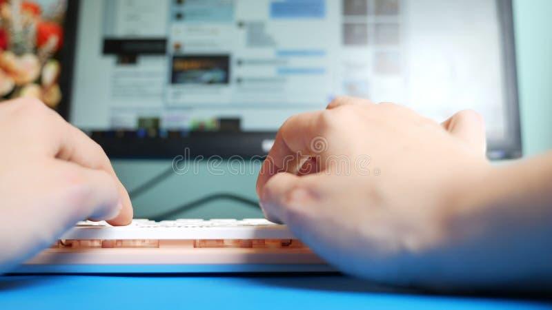 N?rbild F?rsta-personen besk?dar Kvinnliga h?nder som skriver p? rosa meddelanden f?r ett tangentbord i sociala n?tverk, mot bakg arkivfoton