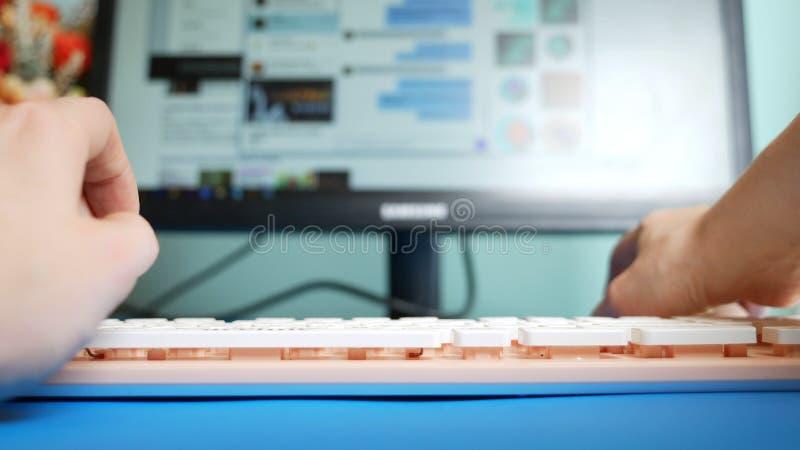 N?rbild F?rsta-personen besk?dar Kvinnliga h?nder som skriver p? rosa meddelanden f?r ett tangentbord i sociala n?tverk, mot bakg arkivfoto