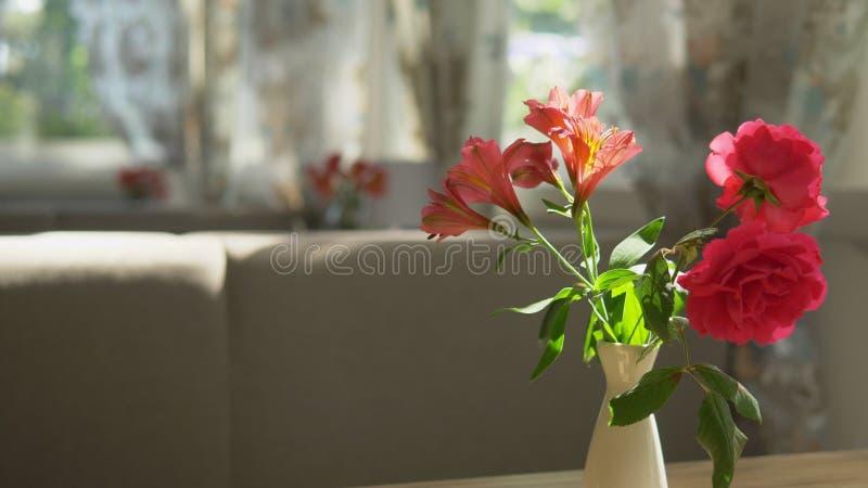 N?rbild Gullig bukett av r?da rosor och freesia i en vas p? en tabell p? en solig sommardag i ett kaf? royaltyfri bild