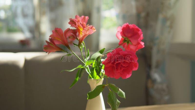 N?rbild Gullig bukett av r?da rosor och freesia i en vas p? en tabell p? en solig sommardag i ett kaf? royaltyfria bilder