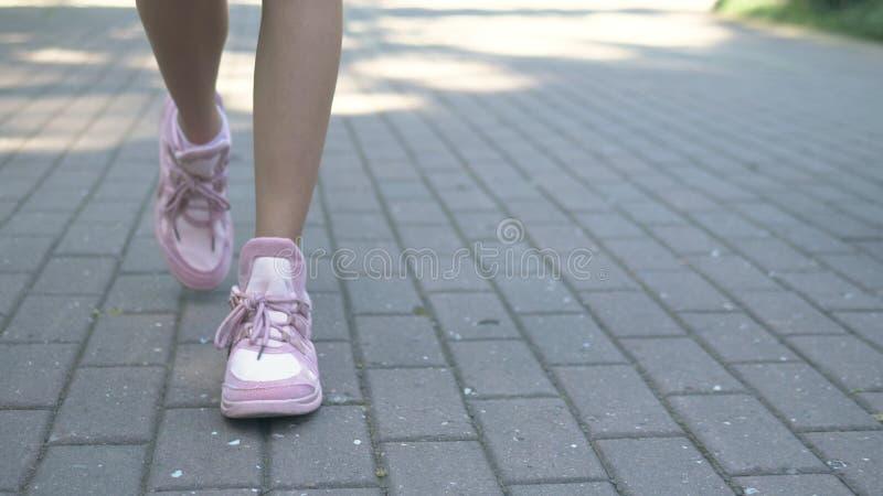 N?rbild kvinnliga ben i stilfulla rosa gymnastikskor flicka som g?r p? gatan med trottoar Naturligt soligt dagsljus arkivbild