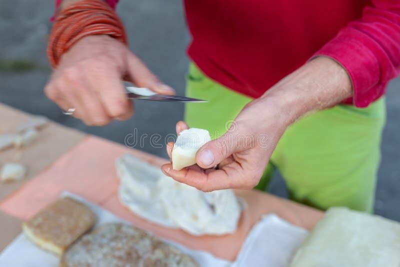 N?rbildb?nder r?cker att klippa skivan av smaklig ?ldrig hemlagad ost p? lantg?rdmatm?ssan arkivfoto