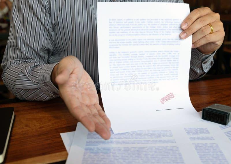 N?rbildbilder av h?nderna av aff?rsm?n som undertecknar och st?mplar i godk?nda avtalsformer arkivbilder