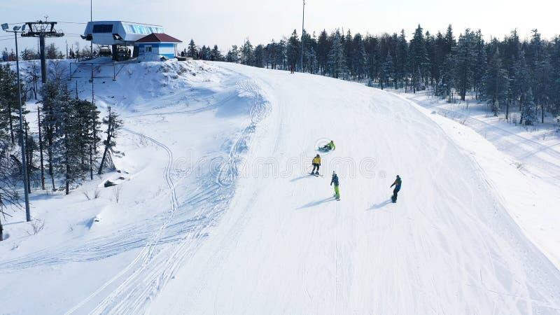 N?rbilden av skidar lutningen och den folkskid?kning och snowboardingen ner av ett sp?r n?ra barrskog i vinter footage skida arkivfoton