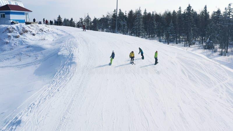 N?rbilden av skidar lutningen och den folkskid?kning och snowboardingen ner av ett sp?r n?ra barrskog i vinter footage skida royaltyfri foto
