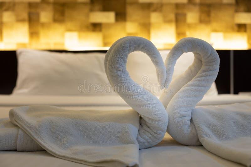 N?rbilden vek svanf?geln av nya vita badlakan p? s?ngarket i hotellet royaltyfria bilder