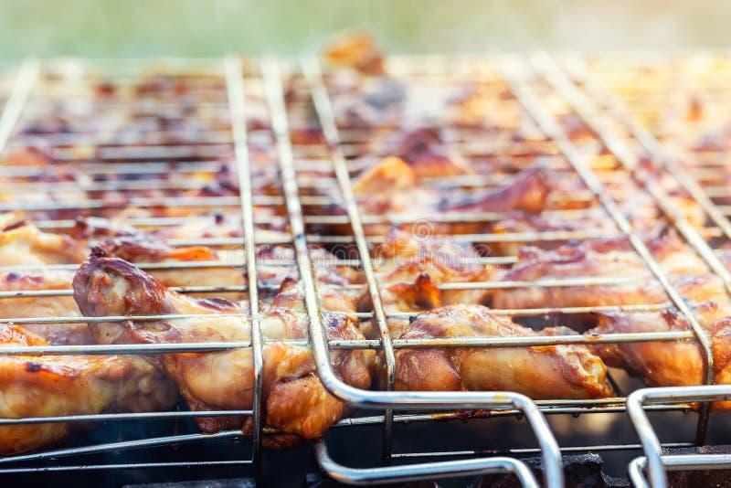 N?rbildh?navingar som lagar mat i metallgrillfestraster p? gallerfyrpanna Det fria tillbringar veckoslutet partiet p? tr?dg?rd Sm royaltyfri bild