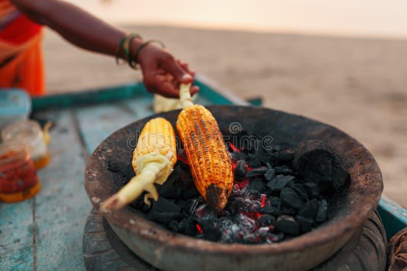 N?rbildh?nder av den kvinnliga gatuf?rs?ljaren gnider en grillad majsmajskolv med citronen och kryddor Indiskt gatamatbegrepp, arkivfoton
