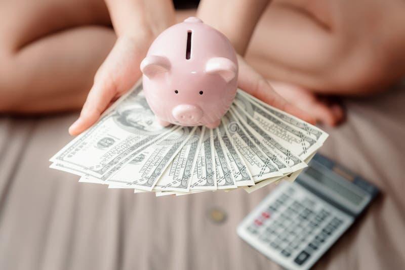 N?rbildkvinnah?nder rymmer pengarkassa och spargrisen i hennes sovrum, den rosa Piggy besparingen, den finansiell aff?ren som pac royaltyfri foto