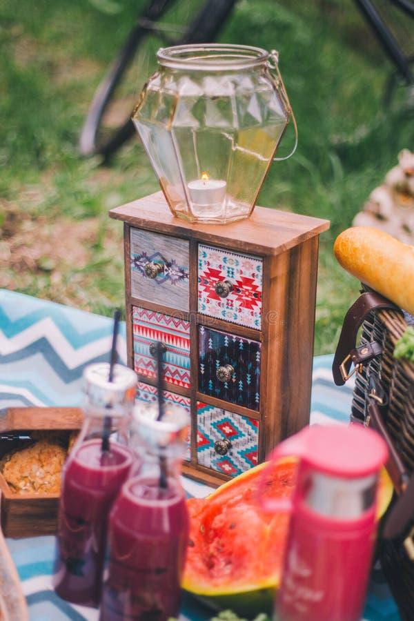 N?rbildpicknick i natur En stearinljus i en ljusstake st?r p? en liten sk?nk, bredvid den ligger mat - vattenmelon, druvakex, fotografering för bildbyråer