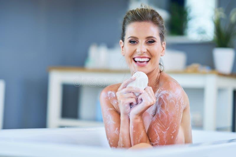 N?rbildst?ende av en ung kvinna som kopplar av i bathtuben fotografering för bildbyråer
