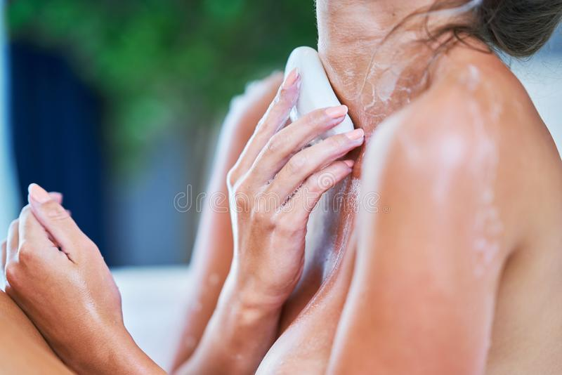 N?rbildst?ende av en ung kvinna som kopplar av i bathtuben arkivbilder