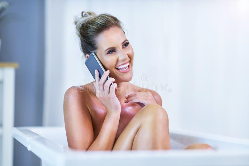 N?rbildst?ende av en ung kvinna som kopplar av i bathtuben royaltyfri foto