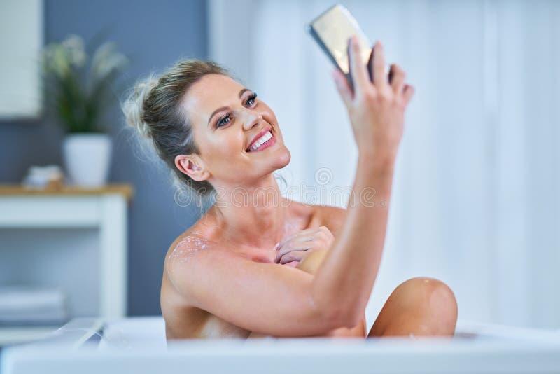 N?rbildst?ende av en ung kvinna som kopplar av i bathtuben arkivbild