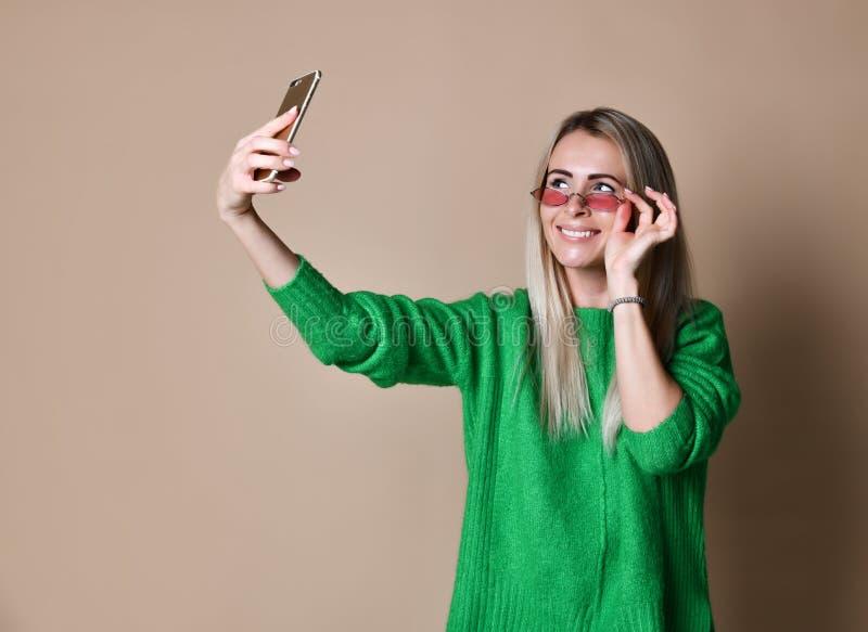 N?rbildst?enden av den blonda kvinnan f?r ungt gladlynt mode i tr?jakl?der g?r selfie p? smartphonen, ?ver beige bakgrund arkivbild