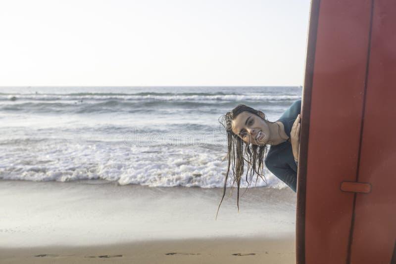 N?tt br?nningflicka med en longboard p? stranden arkivfoto