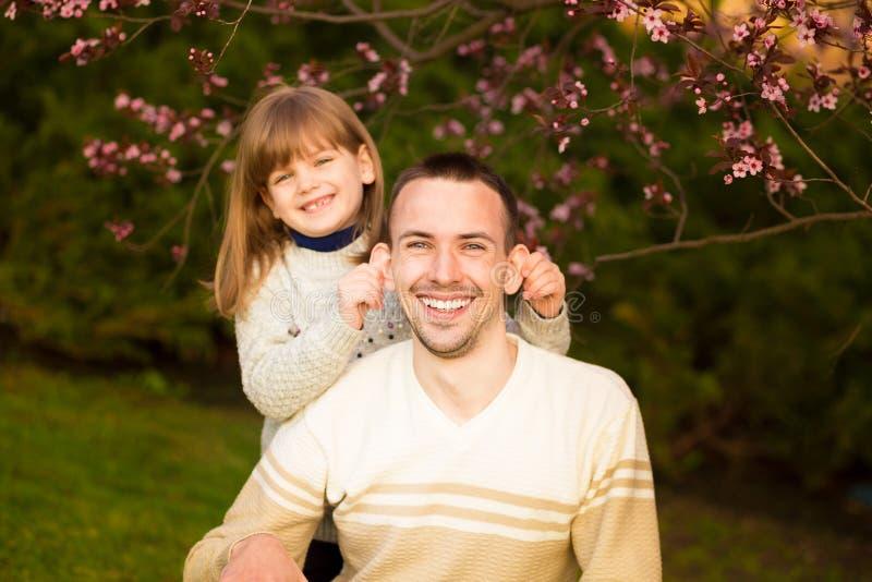 N?tt dotter f?r n?ra ?vre st?ende som omfamnar den Caucasian fadern Familjen tycker om f?r att spendera tid tillsammans arkivbild