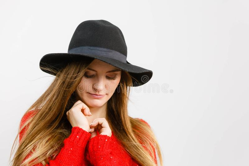 N?tt flicka med brunt h?r och den svarta hatten royaltyfria bilder