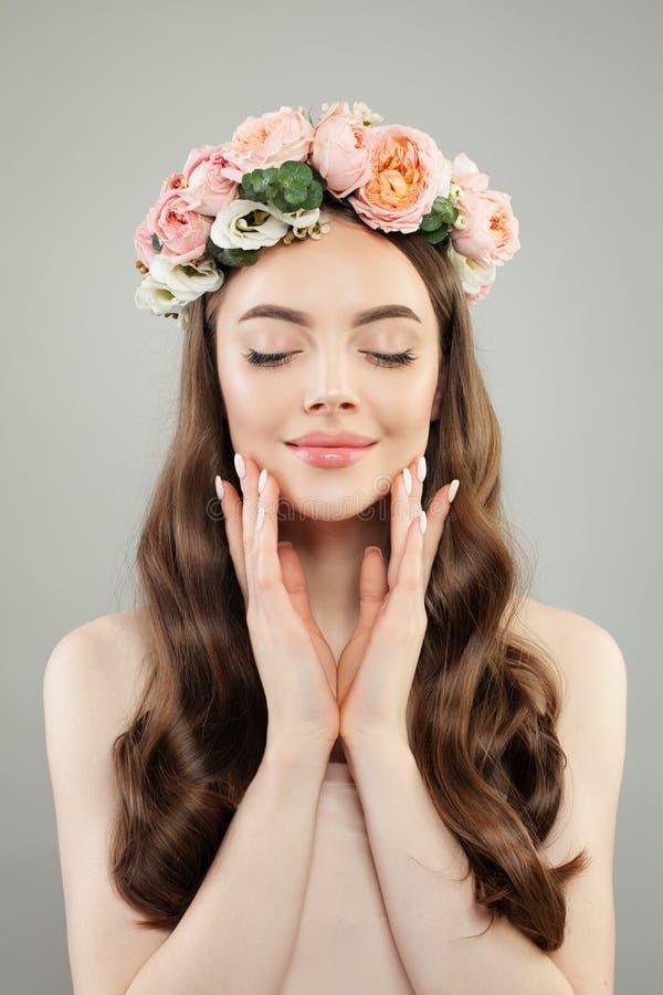 n?tt kvinna f?r st?ende Koppla av modellen med klar hud, långt lockigt hår och blommor royaltyfri bild