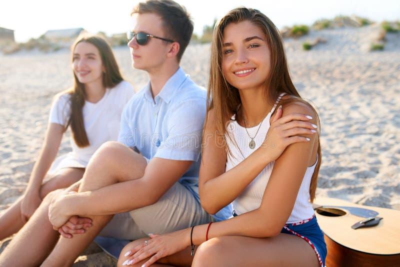 N?tt kvinna som kopplar av med v?nner som sitter p? strandhandduken n?ra havet och solbada Attraktivt brunbr?nt le f?r modell royaltyfri foto
