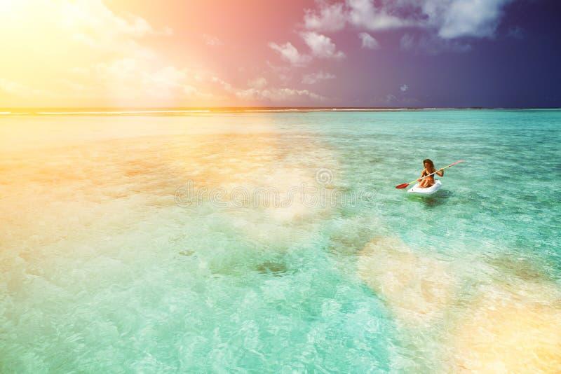 N?tt kvinnasimning i kanot och att koppla av i havet Lycklig ?livsstil Vit sand, kristall-bl?tt hav av den tropiska stranden royaltyfri foto