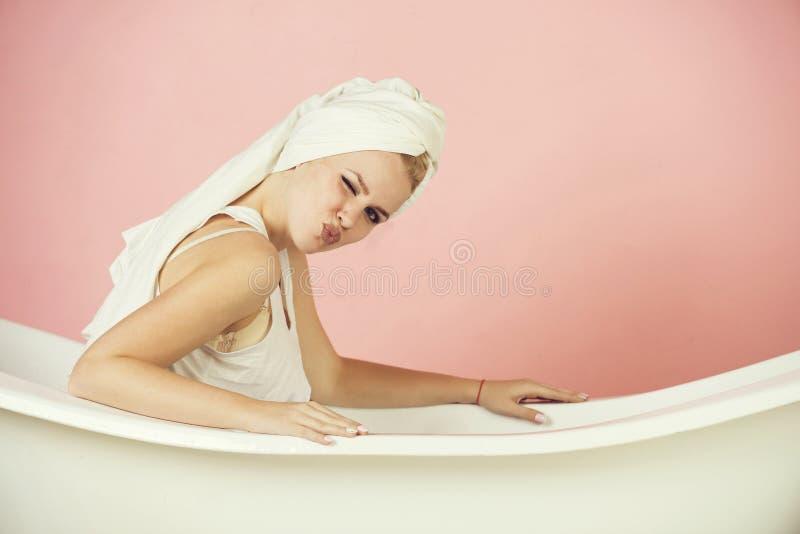 n?tt sexig kvinna med handdukturbansammantr?de i det vita badkaret arkivbilder