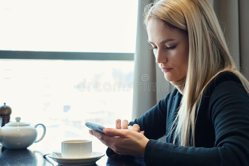 N?tt ung blond flicka med telefonen som sitter p? en tabell i ett kaf? royaltyfria foton