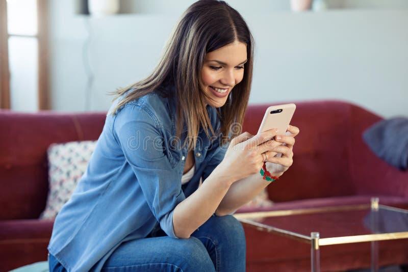 N?tt ung kvinna som anv?nder hennes mobiltelefon, medan sitta p? soffan hemma royaltyfria foton