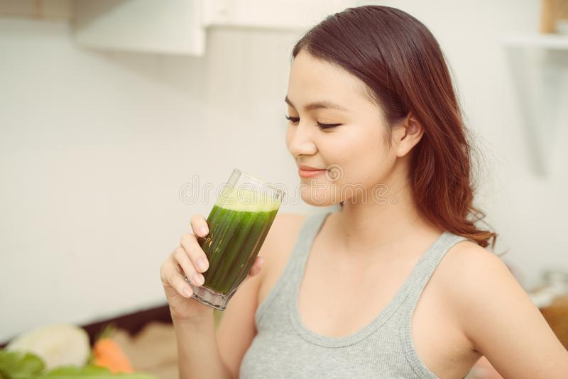 N?tt ung kvinna som dricker en gr?nsaksmoothie i hennes k?k royaltyfri foto
