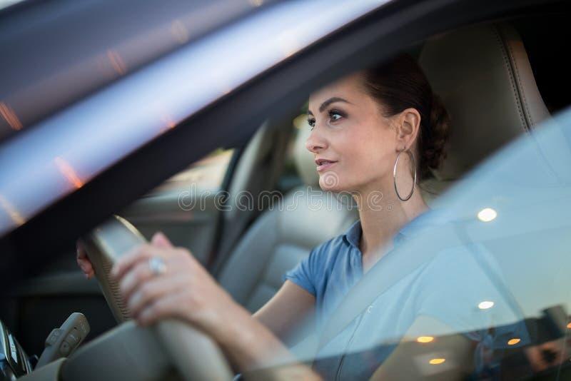 N?tt ung kvinna som k?r en bil arkivbilder