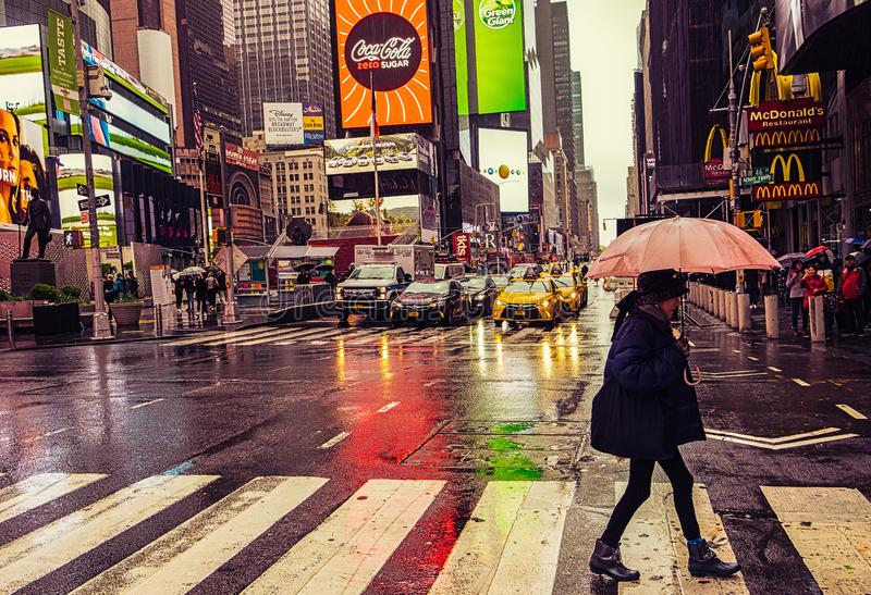 N.Y.C-W46th St & 7th Ave. New York City, U.S.A, May 2019, woman crossing the road on a raining day on W46th St & 7th Ave, Manhattan stock image