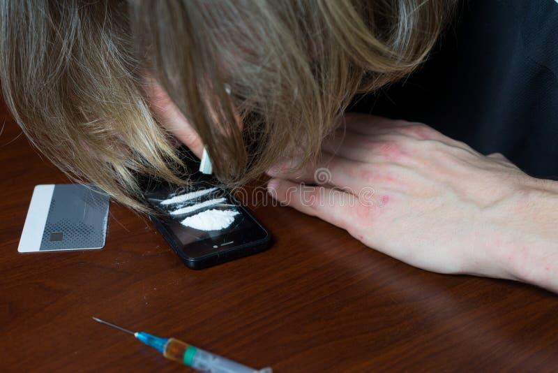 Nałogowiec przy stołem używa kokainę Pojęcie przeciw lekom zdjęcia royalty free