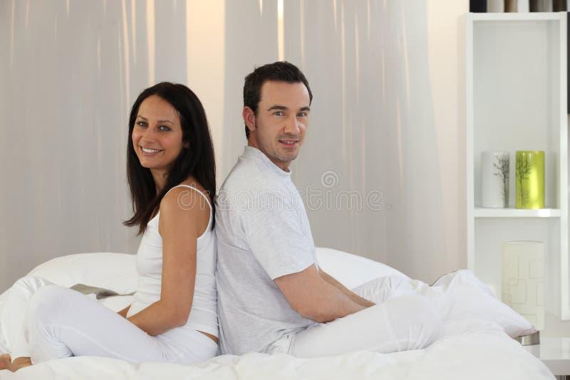 Na łóżku pary obsiadanie zdjęcia stock