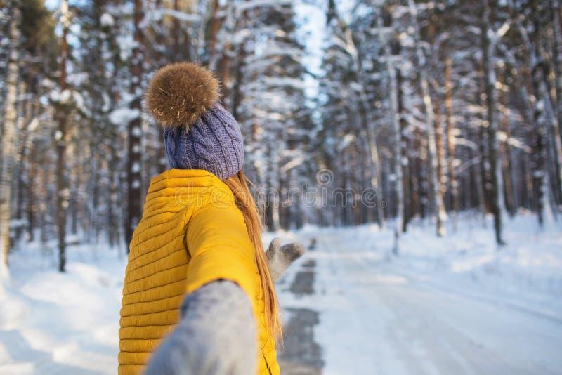 Na aan een jong meisje in heldere kleren die zich in een de winterbos bevinden stock afbeeldingen