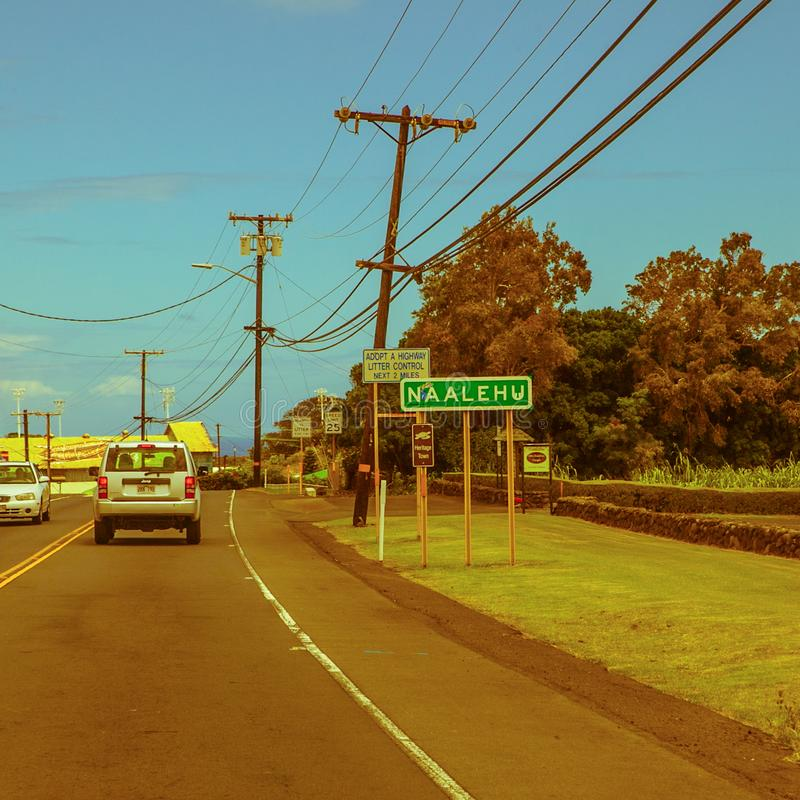 Na Alehu limit city sign road town hawaii. Na Alehu, United States - September 07, 2012 : A car is driving on the island road into Na Alehu village royalty free stock images