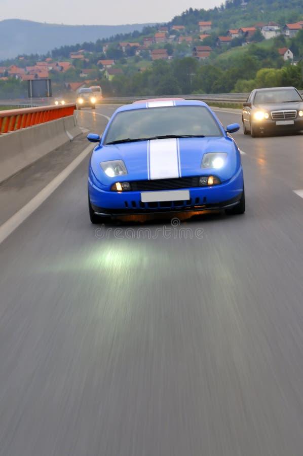 Na autostradzie błękitny szybki bieżny samochód obrazy stock