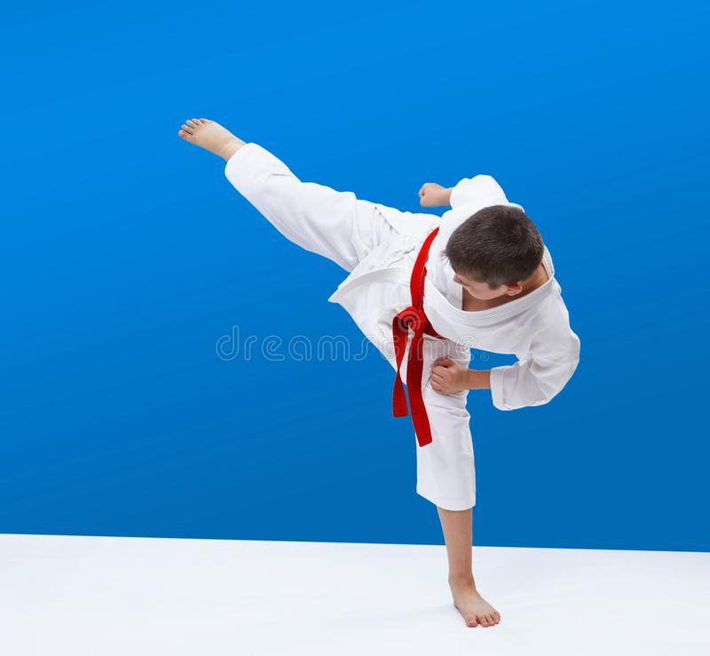 Na błękita tła chłopiec karate bije cios nogę obrazy royalty free