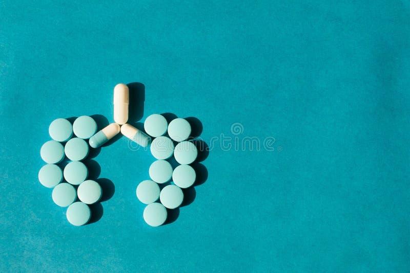 Na błękitnym tle od pastylek forma ludzcy płuca kłaść out Pojęcie lekarstwo dla płuca obraz stock