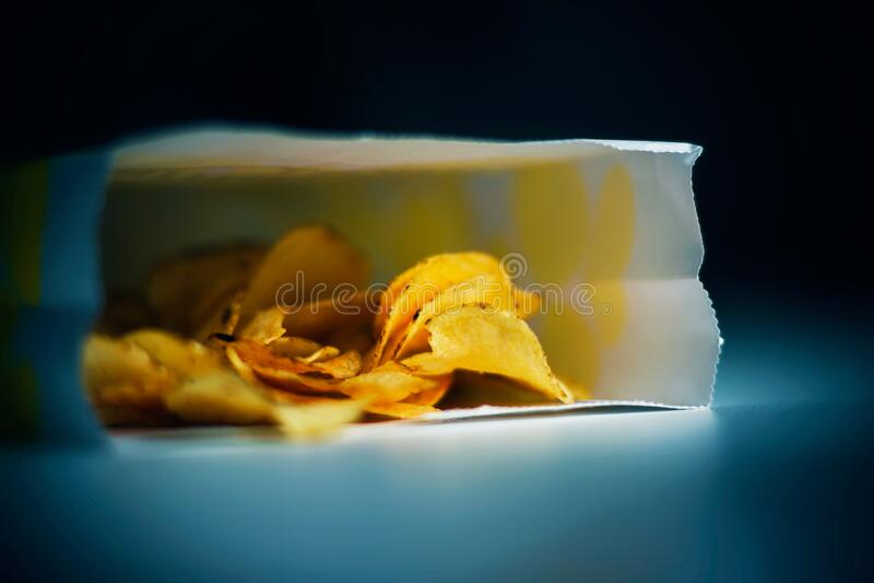 Na białym stole jest papierowa torba chipów, oświetlona przez niebieskie światło z telewizora w nocy obrazy royalty free