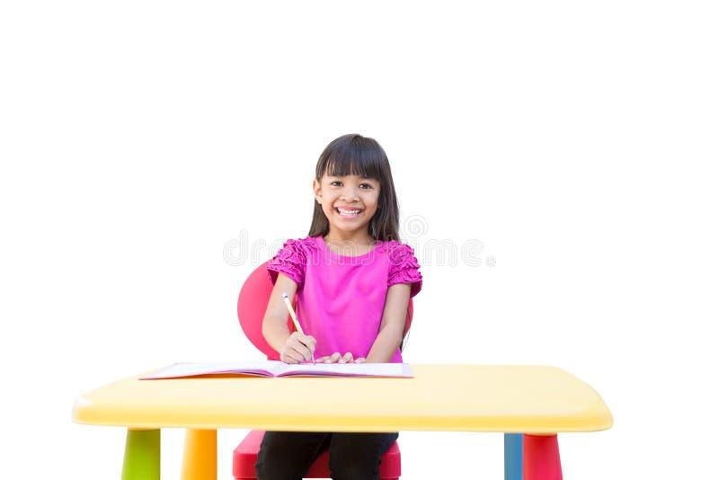 Na biurku małej dziewczynki uśmiechnięty writing obraz royalty free