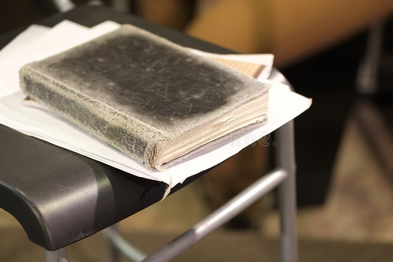 Na borda da cadeira preta é um livro gasto velho fotos de stock royalty free