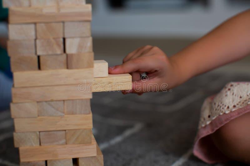 Na cafetaria as mãos na tabela dobraram o enigma Jogue o jenga na tabela, tol de madeira, jogos dos pares fotografia de stock