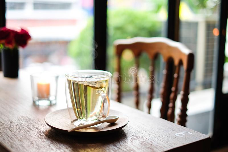 Na cafetaria, o chá quente da alfazema no saque de vidro com colher de madeira & os pires na tabela com a cadeira para relaxam e  fotografia de stock