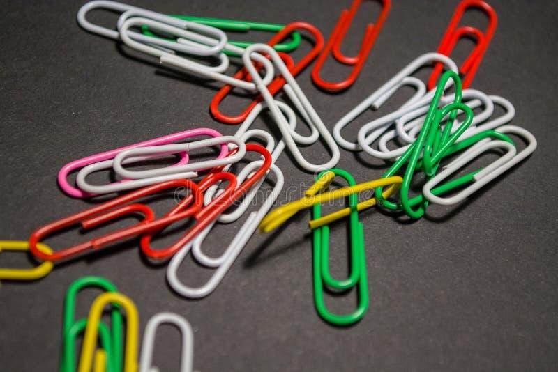 Na czarnym monophonic tle plastikowe barwić papierowe klamerki są kłamstwem Biel, czerwień, zieleń, kolor żółty barwi officemates obraz stock