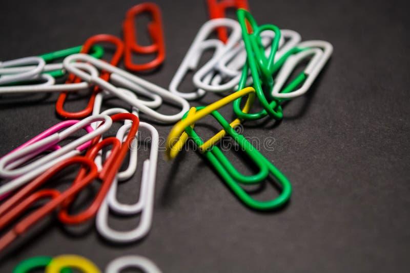 Na czarnym monophonic tle plastikowe barwić papierowe klamerki są kłamstwem Biel, czerwień, zieleń, kolor żółty barwi officemates zdjęcia royalty free