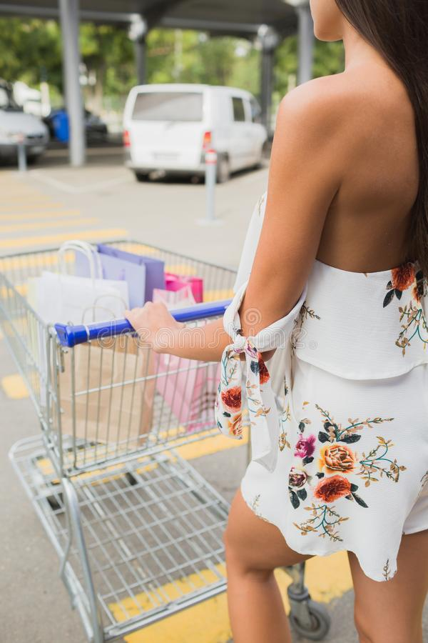Na dag die in de wandelgalerij winkelen Close-up van jonge vrouw dragende het winkelen zakken in een karretje, stock afbeeldingen