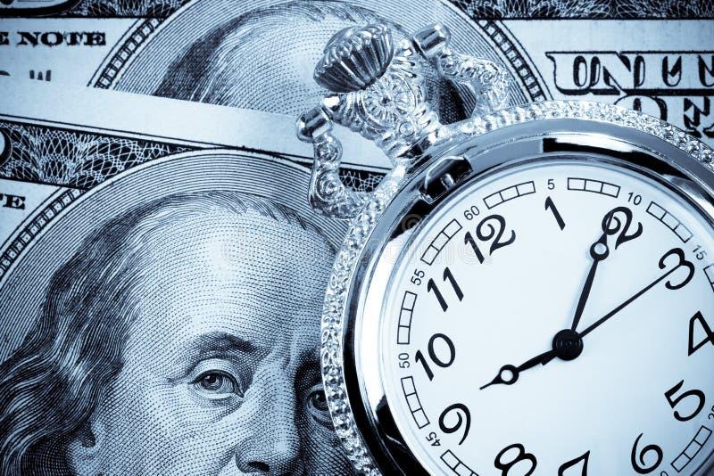 Na dolarowych banknotach złocisty zegarek zdjęcie stock