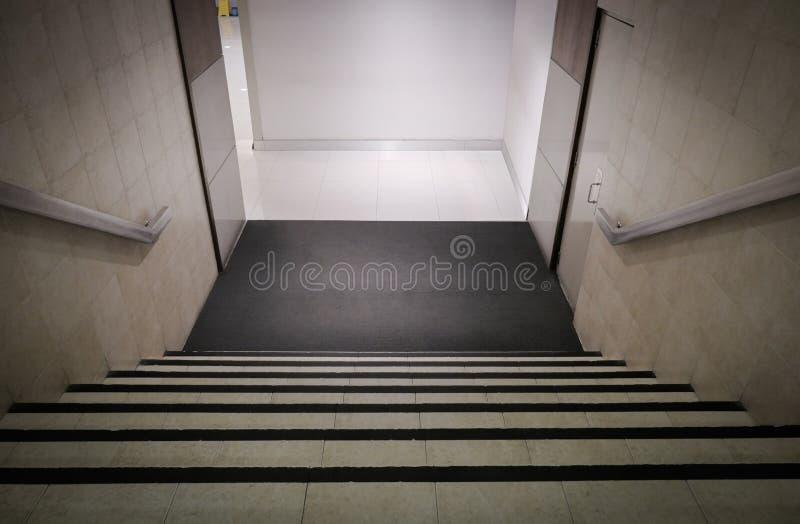 Na dole , wewnętrzne schody biurowe,stopnie w dół kąt perspektywy spadający w kierunku podłogi , wejście z schodkami w dół obrazy royalty free