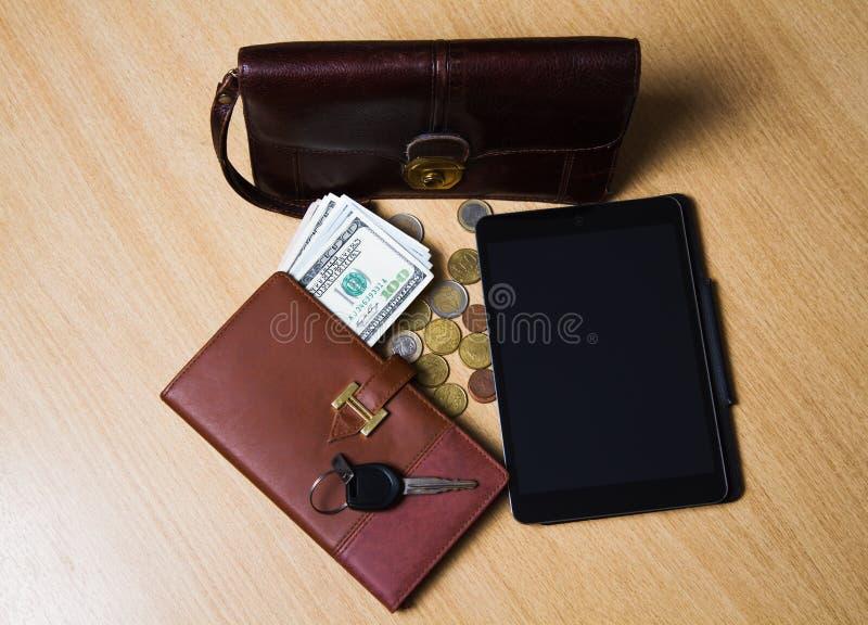 na drewnianego stołu nieatutowym pieniądze, notatniku, pastylce, przydatnej torbie i kluczach samochód, obrazy stock