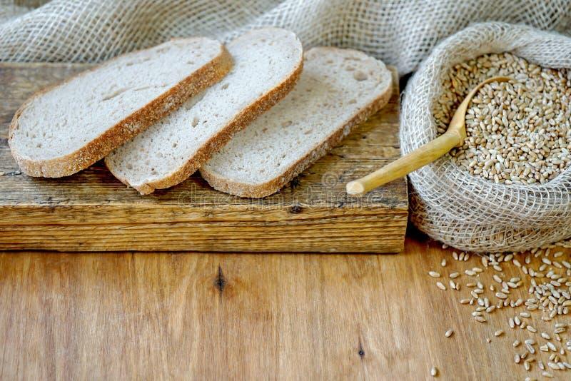 Na drewnianej deski kłamstwa plasterkach chleb W pobliżu jest worek banatka zdjęcie stock
